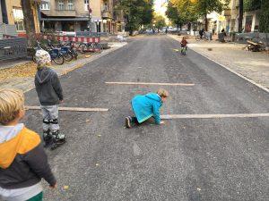 KInder legen auf der Straße Latten zur Verkehrsbreuhigung aus