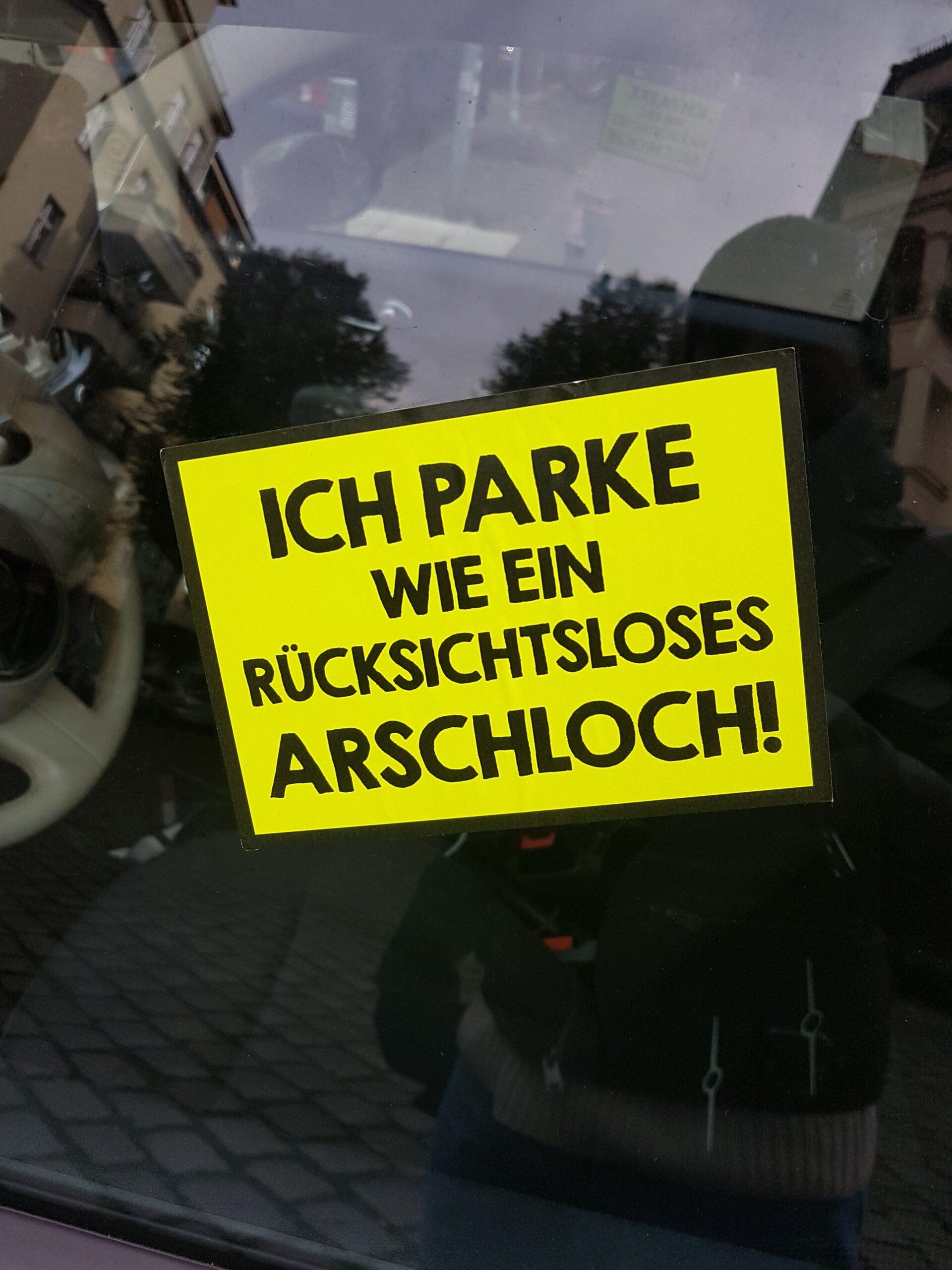 """Bild eines Stickers mit dem Satz """"Ich parke wie ein rücksichtsloses Arschloch"""" an einer Autoscheibe"""